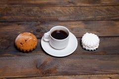 Белая чашка горячего кофе и белые зефиры и пирожные Стоковые Фото