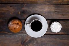 Белая чашка горячего кофе и белые зефиры и пирожные Стоковое фото RF