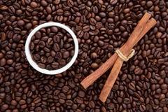 Белая чашка зажаренных в духовке кофейного зерна и циннамона na górze положения квартиры Стоковое Изображение RF