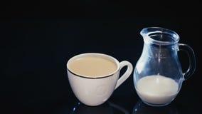 Белая чашка кофе и кувшин молока на черной предпосылке акции видеоматериалы