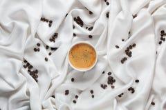 Белая чашка кофе на белой silk ткани Кофейная чашка эспрессо Разбросанные кофейные зерна на белой silk ткани Стоковая Фотография RF