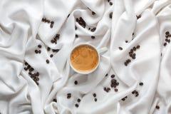 Белая чашка кофе на белой silk ткани Кофейная чашка эспрессо с пеной в форме стороны smiley Разбросанные кофейные зерна Стоковое фото RF