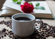 Белая чашка кофе, с кофейными зернами на предпосылке книг Стоковые Фотографии RF