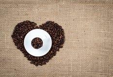 Белая чашка на кофейных зернах сердца Стоковые Фото