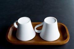 Белая чашка на черной таблице Стоковые Фотографии RF