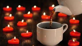 Белая чашка с горячим кофе на предпосылке горящих свечей сток-видео