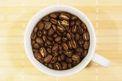 Белая чашка с зажаренными в духовке кофейными зернами Стоковое фото RF