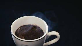 Белая чашка с кофе на черной предпосылке, приходить пара акции видеоматериалы