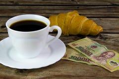 Белая чашка черного кофе, круассана и въетнамских денег Стоковые Изображения