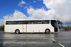 Белая шина тренера ждет пассажиров на туманном ненастном утре стоковое изображение