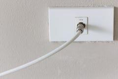 Белая штепсельная вилка ТВ на белой стене Стоковое Изображение