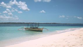 Белая шлюпка bangca в чистой воде бирюзы поставленной на якорь на пляже с белым песком видеоматериал