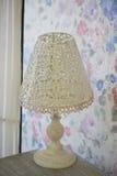 Белая openwork настольная лампа металла стоит на прикроватном столике яркий интерьер шик затрапезный стоковые изображения
