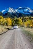 Белая SUV drivews проселочная дорога 12 вниз из Ridgway Колорадо к горам Сан-Хуана с цветом осени Стоковые Фото
