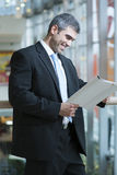 белизна бизнесмена предпосылки изолированная документом читая Стоковые Изображения