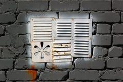 Белизна покрасила окно сброса металла в серой кирпичной стене стоковые фотографии rf