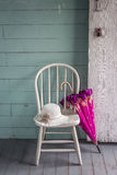 Белизна покрасила стул с розовой склонностью зонтика против ее Стоковые Изображения RF