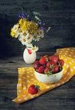 Белизна с красочной салатницей горохов с клубниками на желтой салфетке и вазой с wildflowers Деревянная предпосылка, деревенский  стоковое изображение