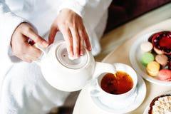Белизна чайника и чашка вручите лить чай в чашку печенья на предпосылке Стоковые Изображения RF