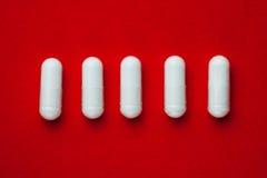 Белизна capsules пилюльки на красной предпосылке Стоковые Фото