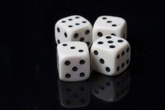 Белизна 4 dices в черной предпосылке Стоковые Изображения