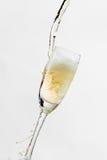 Белое вино брызгая из изолированного стекла, на белой предпосылке Стоковая Фотография