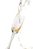 Белое вино брызгая из изолированного стекла, на белой предпосылке Стоковые Изображения RF