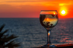 Белое вино на предпосылке моря захода солнца стоковые изображения rf
