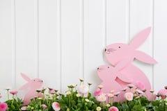 Белое деревянное украшение пасхи с цветками и розовый зайчик для Стоковая Фотография