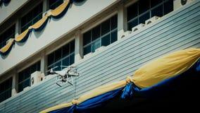 Белое летание трутня на фронте здания с backgroun softfocus Стоковое фото RF