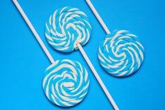 3 белое и голубые леденцы на палочке на голубой предпосылке Стоковая Фотография RF