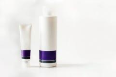 2 белое и фиолетовая пластмасса разливают заботу по бутылкам кожи fpr Стоковая Фотография