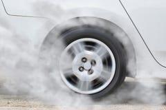 Белое колесо автомобиля перемещаясь и куря Стоковые Изображения RF