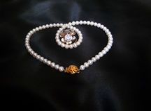 Белое ожерелье жемчуга с кольцами на черной шелковистой предпосылке стоковое фото rf
