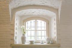 Белое окно с белым комплектом чая в старом русском имуществе Стоковые Фотографии RF
