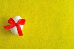 Белое пасхальное яйцо с красным смычком Стоковое Изображение
