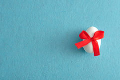 Белое пасхальное яйцо с красным смычком Стоковые Фото