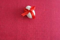 Белое пасхальное яйцо с красным смычком Стоковые Фотографии RF