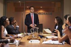 Белое положение бизнесмена для того чтобы адресовать коллег на встрече Стоковое фото RF