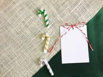 Белое рождество бумаги и конфеты карточки на дерюге - зеленой ткани Стоковые Фотографии RF