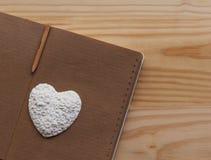 Белое сердце лежа на тетради Стоковая Фотография