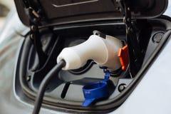 Белое электрическое сопло будучи затыканным в e-автомобиль Стоковая Фотография RF