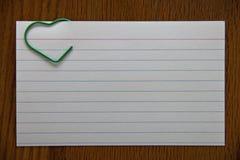 Белое notecard с зеленым зажимом сердца Стоковая Фотография