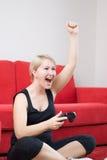 Белокурая девушка выигрывает на видеоиграх Стоковая Фотография RF