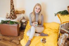 Белокурая девушка выпивая ее кофе, ест печенья и прочитала книгу Стоковое Фото