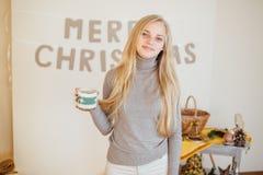 Белокурая девушка выпивая ее кофе, ест печенья и прочитала книгу Стоковое Изображение RF