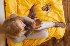 Белокурая девушка выпивая ее кофе, ест печенья и прочитала книгу Стоковая Фотография RF