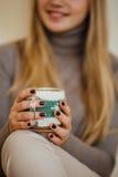 Белокурая девушка выпивая ее кофе, ест печенья и прочитала книгу Стоковые Фото
