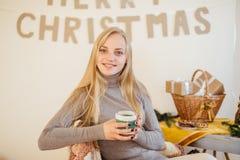 Белокурая девушка выпивая ее кофе, ест печенья и прочитала книгу Стоковое фото RF