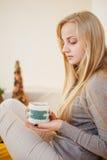 Белокурая девушка выпивая ее кофе, ест печенья и прочитала книгу Стоковое Изображение
